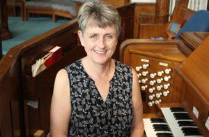Nancy Martin, Music Director, Sitting at the organ.